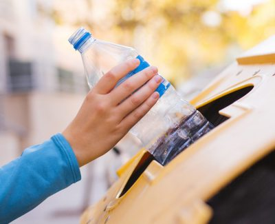 Stock photo of a woman's hand recycling a plastic bottle in a yellow container to save the environment
